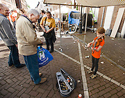 Een man geeft geld aan de viool spelende Oskar op de vrijmarkt in Utrecht tijdens Koninginnedag 2012.<br />