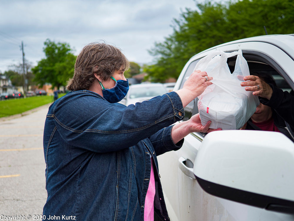 21 MAY 2020 - DES MOINES, IOWA: MELISSA GRADISCHNIG, from Central Iowa Shelter Services, hands a bag of meals to people in a drive through emergency food distribution in Evelyn K. Davis Park in central Des Moines. All of the 485 meals were distributed in about an hour. The economic fallout of the pandemic is being felt throughout Iowa. On May 21, 2020, Iowa reported that 187,375 people had filed for unemployment since the beginning of the COVID-19 pandemic and resulting economic shutdown. Emergency food pantry has also increased in that time, as many Iowans in low wage jobs used emergency food banks and pantries for the first time. The Food Bank of Iowa said Thursday that demand in April 2020 was 31% higher than demand in April 2019, mostly because of unemployment caused by the Coronavirus (SARS-CoV-2) pandemic. The emergency food distribution Thursday was organized by the city of Des Moines, Food Bank of Iowa, Central Iowa Shelter and Services, Urban Dreams and Orchestrate Hospitality.      PHOTO BY JACK KURTZ