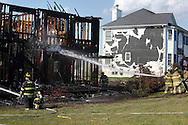 Vails Gate firefighters work at the scene of a fire that destroyed a house on Independence  Drive on Friday, Aug. 16, 2013. Heat from the fire melted the siding on the house at right.