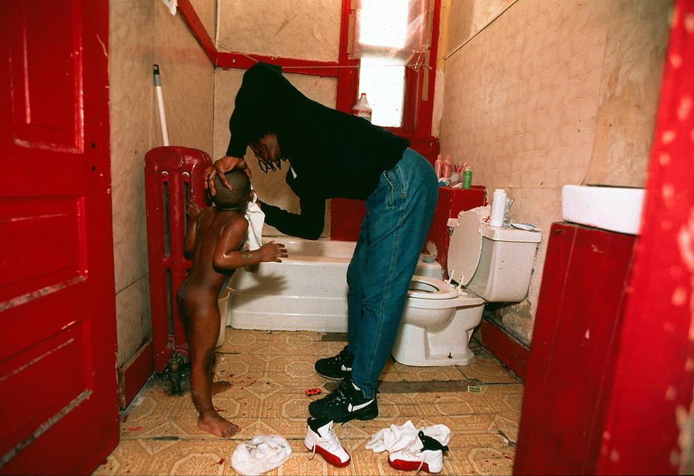 A welfare receipient gives one of her children a bath.