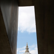 Partial view of St. Paul's Cathedral from in  between a concrete built structure.