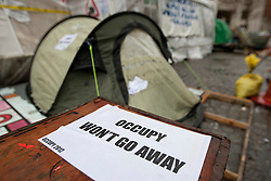 "© licensed to London News Pictures. London, UK 22/02/2012. A tent at Occupy London tent city is pictured next to a sign which reads ""Occupy won't go away"" as the protest group lost their court case and refused permission to appeal against their eviction from the Occupy London camp outside St Paul's Cathedral. Photo credit: Tolga Akmen/LNP"