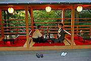 In a traditional Japanese setting, a couple shares a snack in a teahouse at a Kyoto temple. Japan. Hungry Planet: What the World Eats (p. 185). This image is featured alongside the Ukita family images in Hungry Planet: What the World Eats.