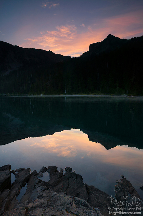 Fay Peak and red cirrus clouds and reflected at sunrise in Mowich Lake, Mount Rainier National Park, Washington. Fay Peak, named for Fay Fuller, the first woman to climb Mount Rainier, has an elevation of 6,492 feet (1,979 meters).