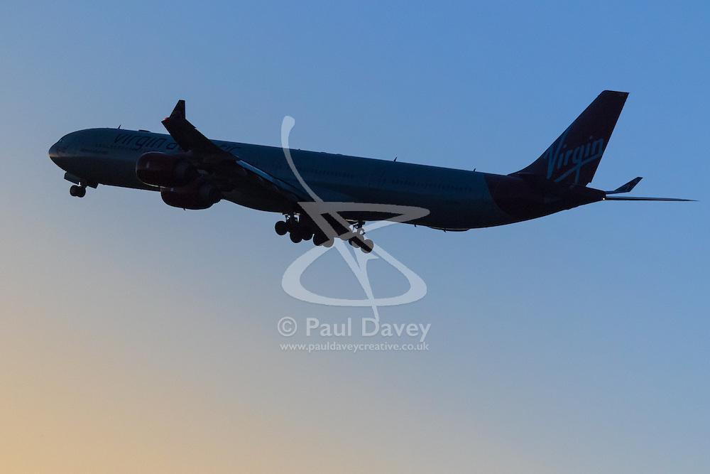 A Virgin Atlantic Airbus A340-600 departs from London Heathrow's runway 27L, into a darkening sky.