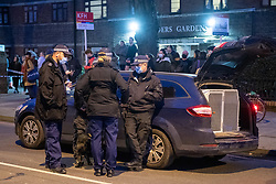 © Licensed to London News Pictures. 09/03/2021. London, UK. Police dog handlers  wait next to a cordon after Metropolitan Police closed off Poynders Road in what is believed to be connected to the search for missing person Sarah Everard. Photo credit: Peter Manning/LNP