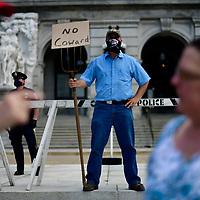 """HARRISBURG, PA - MAY 15:  A Trump supporter holds a sign on a pitchfork stating """"No Coward"""" during a rally outside the Pennsylvania Capitol Building to protest the continued closure of businesses due to the coronavirus pandemic on May 15, 2020 in Harrisburg, Pennsylvania.  Pennsylvania Governor Tom Wolf has introduced a color tiered strategy to reopen the state with most areas not easing restrictions until June 4.  (Photo by Mark Makela/Getty Images)"""