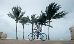 A man rides his bike along the beach with blowing winds and threatening skies in anticipation for Hurricane Irma, in Hollywood, Fla., Saturday, September 9, 2017. THE CANADIAN PRESS/Paul Chiasson