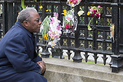 Westminster, London, March 27th 2017. A man examines the flowers attached to the railings surrounding Parliament. Credit: ©Paul Davey<br /> <br /> ©Paul Davey<br /> FOR LICENCING CONTACT: Paul Davey +44 (0) 7966 016 296 paul@pauldaveycreative.co.uk