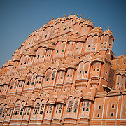 """Hawa Mahal ot the """"Palace of Winds"""", is a palace in Jaipur, India. It was built in 1799 by Maharaja Sawai Pratap Singh, and designed by Lal Chand Usta  in the form of the crown of Krishna, the Hindu  god. Its unique five-story exterior is also akin to the honeycomb of the beehive with its 953 small windows called jharokhas  that are decorated with intricate lattice work. The original intention of the lattice was to allow royal ladies to observe everyday life in the street below without being seen, since they had to observe strict """"purdah"""" (face cover)."""