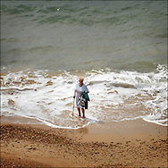 An eldery lady paddles in the sea in Bournemouth..