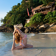 Yoga on the beach at sunrise in pigeon pose, Ko Lipe, Thailand