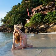 Yoga on the beach at sunrise in pigeon pose, Ko Lipe, Thailand