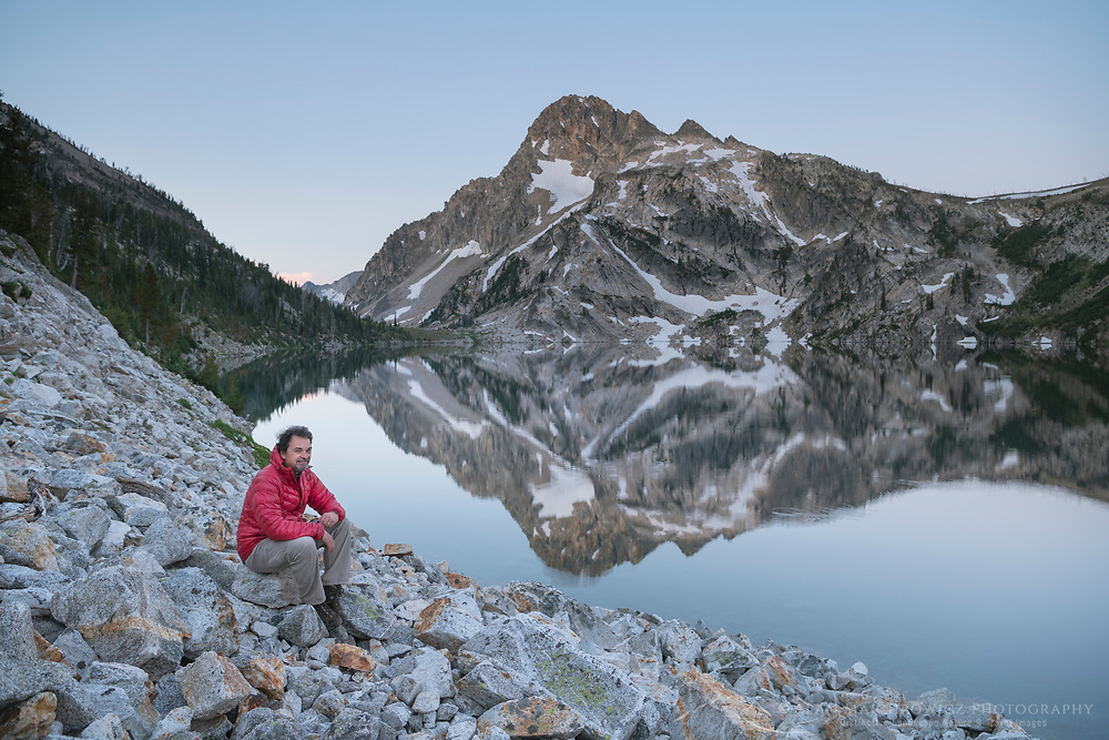 Adult male hiker in red jacket admiring the view of Sawtooth Lake and Mount Regan, Sawtooth Mountains Wilderness Idaho