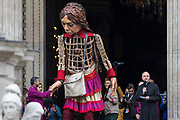 Little Amal, a giant puppet of a Syrian refugee girl fleeing conflict, leaves St Pauls Cathedral after being welcomed by the dean Dr David Ison and a crowd including many children on 23rd October 2021 in London, United Kingdom. The 3.5-metre puppet, which is nearing the end of an 8,000km journey from the Turkish-Syrian border to Manchester in support of refugees, climbed the steps of St Pauls Cathedral to present a wood carving of a ship at sea from St Pauls birthplace at Tarsus in Turkey to the dean.
