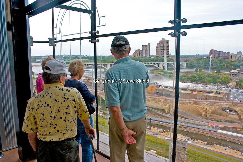 Visitors to the Mill City Museum viewing Mississippi River 3rd Street Bridge and Stone Arch Bridge.  Minneapolis Minnesota USA