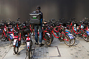 A man working a s a delivery man for Uber Eats rents a bicycle from a rental-bike lot in a street in Otemachi, Tokyo, Japan. Thursday November 5th 2020