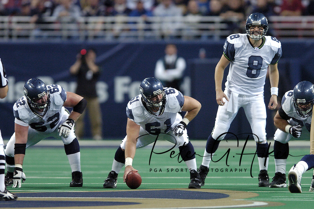 Seattle quarterback Matt Hasselbeck (8) changes the play at the line, as Seahawk line men Chris Gray (62) and Robbie Tobeck (61) listen for the play change, against the St. Louis Rams in St. Louis, Missouri, November 14, 2004.
