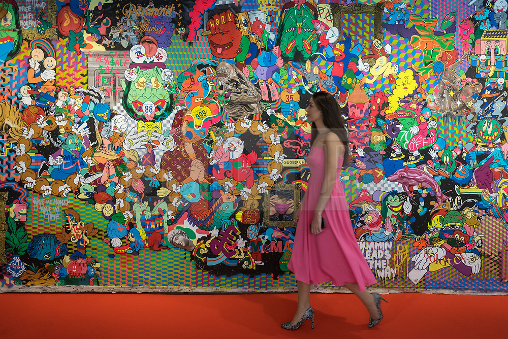 """© Licensed to London News Pictures. 04/10/2018. LONDON, UK. A staff member walks next to """"Speculative Entertainment No 1, London Edition"""" by Uji Hahan Handoko Eko Saputro. Preview of Moniker Art Fair, taking place during Frieze Week at the Old Truman Brewery, near Brick Lane.  Now in its tenth year, the fair embraces contemporary urban art from emerging and established artists  This year, the show's theme is 'Uncensored', shedding light on social, economic and ecological issues, and is open 4 to 7 October.  Photo credit: Stephen Chung/LNP"""