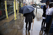 London, UK. Sunday 23rd August 2015. Heavy summer rain showers in the West End. People brave the wet weather armed with umbrellas and waterproof clothing.