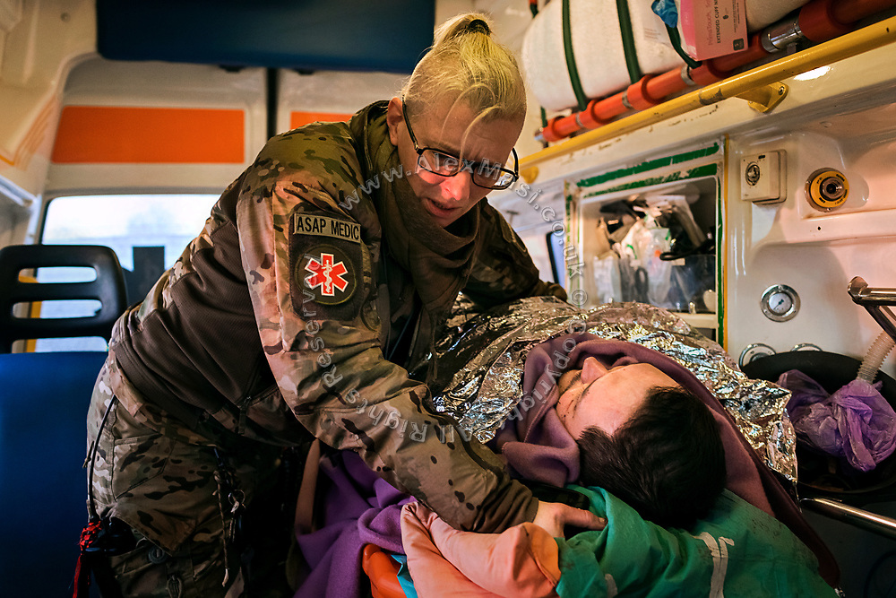 Julia Paevska is evacuating a volunteer named Sergey to a helicopter in Bakhmut, a town in eastern Ukraine's conflict zone, carrying him to a better hospital in the city of Dnipropetrovsk. He was wounded when a sniper bullet hit the van he was driving in Zaitseve, close to the frontline, as he was bringing humanitarian aid to civilians alongside another volunteer, who was also injured.