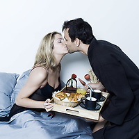 beautiful young caucasian couple in a bed on isolated background having breafast in bed