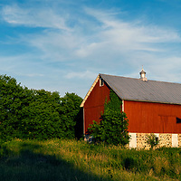 An old farm windmill is cast on the side of an old red barn in a cornfield in Wisconsin