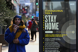 © Licensed to London News Pictures. 02/01/2021. London, UK. A woman speaking on a mobile phone in north London walks past the government's 'Coronavirus Tier 4 - Stay Home' publicity campaign poster, after the mutated variant of the SARS-Cov-2 virus continues to spread around the country. The President of the Royal College of Physicians,Professor Andrew Goddard, has warned that COVID-19 infection cases are set to rise in the coming weeks and that NHS staff and healthcare workers are worried about the challenges against the virus over the coming months. Photo credit: Dinendra Haria/LNP