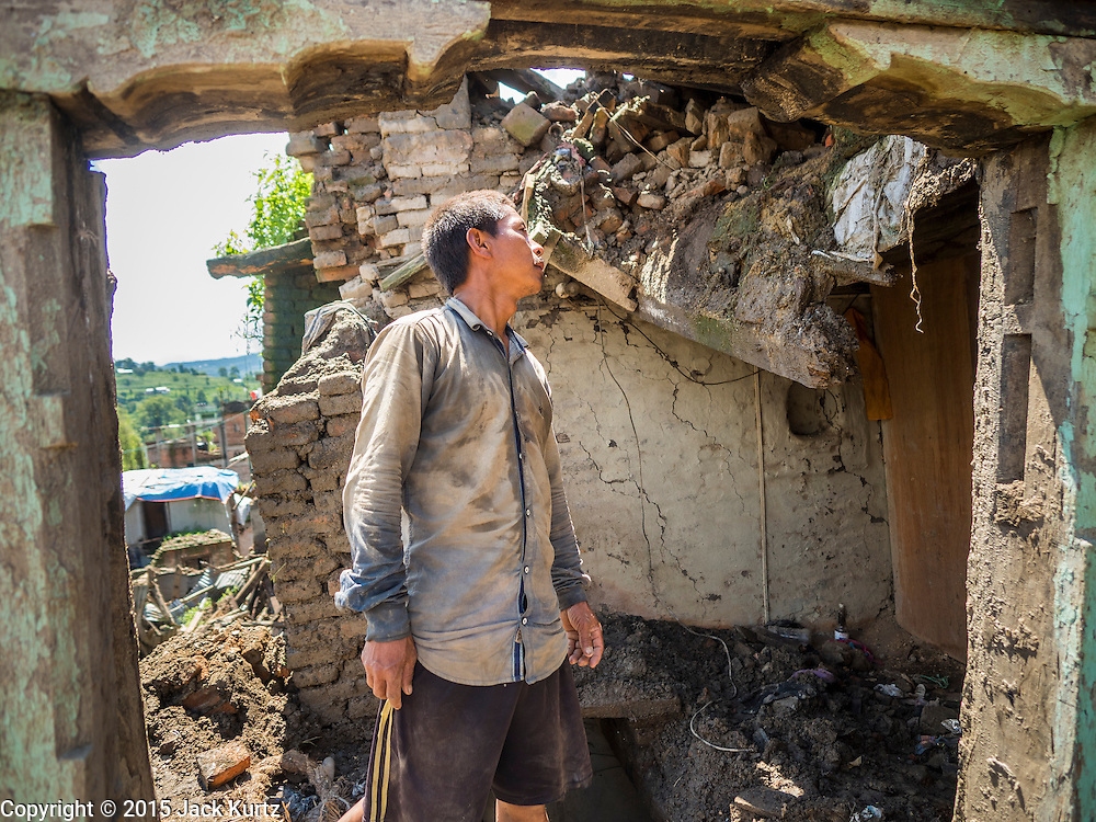 03 AUGUST 2015 - SANKHU, NEPAL:  A laborer looks at a home he was hired to demolish in Sankhu, a community about 90 minutes from central Kathmandu. The home was damaged in the earthquake and the owners hope to rebuild on the site but first half to take down what's left of the existing home. The Nepal Earthquake on April 25, 2015, (also known as the Gorkha earthquake) killed more than 9,000 people and injured more than 23,000. It had a magnitude of 7.8. The epicenter was east of the district of Lamjung, and its hypocenter was at a depth of approximately 15km (9.3mi). It was the worst natural disaster to strike Nepal since the 1934 Nepal–Bihar earthquake. The earthquake triggered an avalanche on Mount Everest, killing at least 19. The earthquake also set off an avalanche in the Langtang valley, where 250 people were reported missing. Hundreds of thousands of people were made homeless with entire villages flattened across many districts of the country. Centuries-old buildings were destroyed at UNESCO World Heritage sites in the Kathmandu Valley, including some at the Kathmandu Durbar Square, the Patan Durbar Squar, the Bhaktapur Durbar Square, the Changu Narayan Temple and the Swayambhunath Stupa. Geophysicists and other experts had warned for decades that Nepal was vulnerable to a deadly earthquake, particularly because of its geology, urbanization, and architecture.    PHOTO BY JACK KURTZ