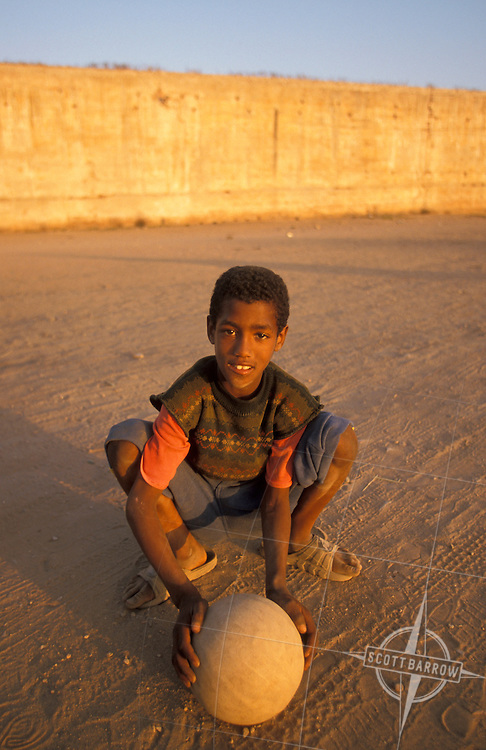 Young Moroccan boy with his soccer ball on a sandlot playground in Rabat, Morocco.
