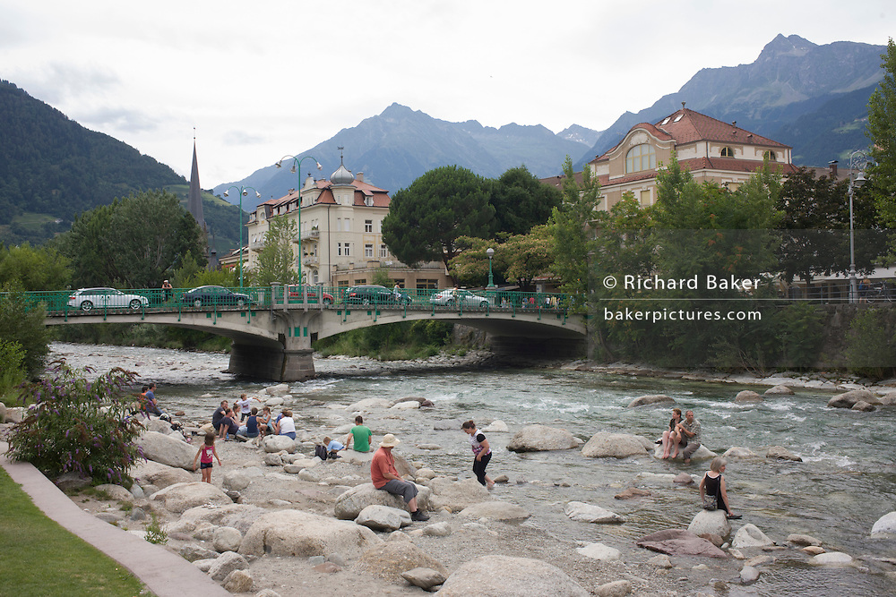 Locals bathe in the Passer River, in the South Tyrolean town of Meran-Merano, best known for its spa resorts, located within a basin, surrounded by mountains standing up to 3,335 metres (10,942 feet) above sea level, at the entrance to the Passeier Valley and the Vinschgau. In the past, the town has been a popular place of residence for several scientists, literary people, and artists, including Franz Kafka, Ezra Pound, and Paul Lazarsfeld, who appreciated its mild climate.