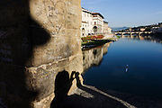 "The shadow of a tourist is seen across a central pillar covered in graffiti on Ponte Vecchio that crosses River Arno, Florence. The names of past visitors are etched on the medieval plaster and beyond is a rower who sculls upstream on the river towards the boating club that lies just beyond the bridge at the water's edge. The Ponte Vecchio (""Old Bridge"") is a Medieval bridge over the Arno River, in Florence, Italy, noted for still having shops built along it, as was once common. Butchers initially occupied the shops; the present tenants are jewellers, art dealers and souvenir sellers. It has been described as Europe's oldest wholly-stone, closed-spandrel segmental arch bridge. To enforce the prestige of the bridge, in 1593 the Medici Grand Dukes prohibited butchers from selling there; their place was immediately taken by several gold merchants."