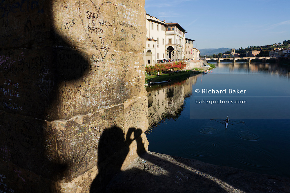 """The shadow of a tourist is seen across a central pillar covered in graffiti on Ponte Vecchio that crosses River Arno, Florence. The names of past visitors are etched on the medieval plaster and beyond is a rower who sculls upstream on the river towards the boating club that lies just beyond the bridge at the water's edge. The Ponte Vecchio (""""Old Bridge"""") is a Medieval bridge over the Arno River, in Florence, Italy, noted for still having shops built along it, as was once common. Butchers initially occupied the shops; the present tenants are jewellers, art dealers and souvenir sellers. It has been described as Europe's oldest wholly-stone, closed-spandrel segmental arch bridge. To enforce the prestige of the bridge, in 1593 the Medici Grand Dukes prohibited butchers from selling there; their place was immediately taken by several gold merchants."""