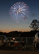 Middletown, New York -  People watch Independence Day fireworks between cars in a parking lot on July 3, 2010.