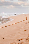 A man leaves footprints in the sand as he walks along a North Shore Beach in Hawaii.