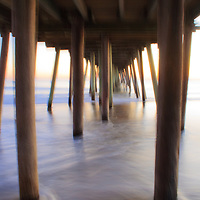 Abstract, blurred image of waves breaking under the fishing pier at sunrise, Virginia Beach, Virginia.