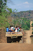 PRIMARY RAINFOREST, Amazon, near Boavista, northern Brazil, South America. People transported by lorry. A red sandy road cuts a path through Primary rainforest. It provides access for people, campesinos, logging and mass crop farming and agriculture. Ecological biosphere and fragile ecosystem where flora and fauna, and native lifestyles are threatened by progress and development. The rainforest is home to many plants and animals who are endangered or facing extinction. This region is home to indigenous primitive and tribal peoples including the Yanomami and Macuxi.