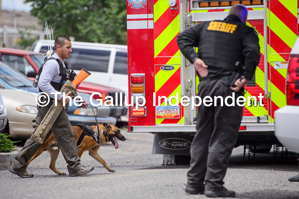 072315       Cable Hoover<br /> <br /> Gallup police K-9 officer Jessie Diaz brings his dog into the jail during a disturbance at the McKinley County Detention Center Thursday.