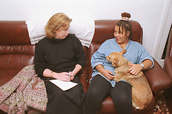 Teenage girl with dog sitting on sofa in living room talking to female social worker,