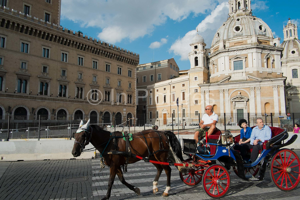 Tourists ride a horse and cart through a square, Rome, Italy.