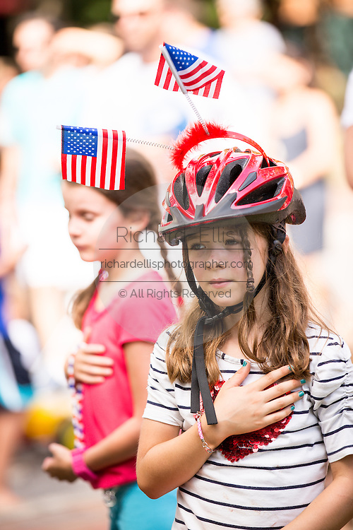 A young girl stand for the national anthem as residents of I'on community celebrate Independence Day with a bicycle and golf cart parade July 3, 2013 in Mt Pleasant, SC.