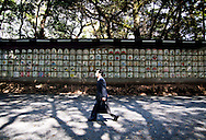 A businessman walks past prayers at the entrance to the Meiji Shrine in Tokyo, Japan.