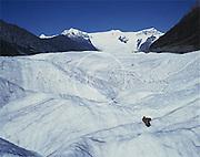 Alaska. Wrangell St Elias National Park. Root glacier hiker enjoys a book and a tan on the Root Glacier.