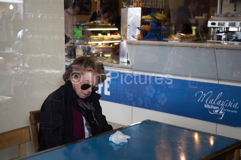 Woman sleeping in a cafe on Portobello Road market in West London, United Kingdom.