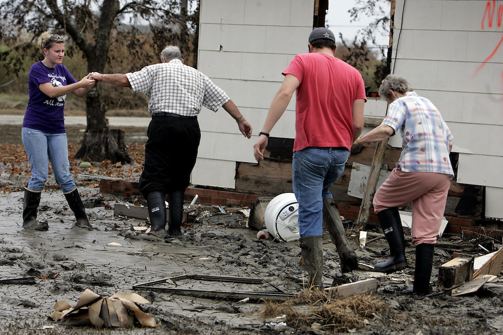 Eric Kile, second from right, and his fiancee Shae Caldwell, left, help Eric's grandparents Earl and Ameda Kile walk across their yard, covered with thick mud and debris, to survey damage to the elderly couple's home after Hurricane Ike in Sabine Pass, Texas, Friday September 19, 2008.