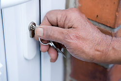 Hand of older woman turning the key in the lock to her front door,