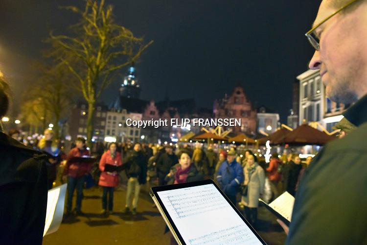 Nederland, Nijmegen, 21-2-2019  In Nijmegen werd het vergissingsbombardement van 75 jaar geleden in 1944 herdacht. Langs de zgnd. brandgrens van de binnenstad stonden tientallen koren en musici die tussen 20.00 uur en 20.15 uur het muziek brachten. Ook bij de honderden met kaarsjes verlichte naamplaatjes die in de straten ingelegd zijn stonden verwanten met soms een foto van hun omgekomen familielid.Foto: Flip Franssen