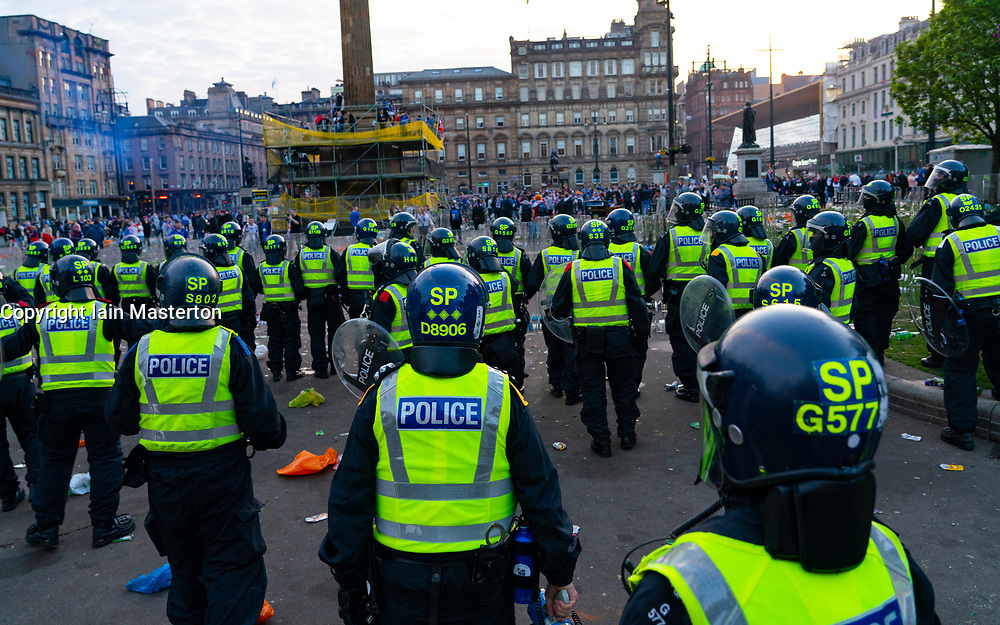 Glasgow, Scotland, UK. 15 May 202. Rangers football supporters  celebrating 55th league victory are cleared from George Square by police in riot gear on Saturday evening. In very violent scenes police were pelted with bottles and items from a nearby construction site as police pushed the supporters into the south west corner of the square. Pic; Police in riot gear enter George Square.  Iain Masterton/Alamy Live News.