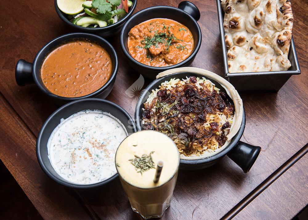 A combination dishes, House Black Daal, Mutton Pepper Fry <br /> Chicken Berry Britania biryani, Kachumber (salad) Raita (yoghurt), Mango lassi<br /> East India Gimlet at Dishoom, High Street Kensington as part of a restaurant review.  <br /> Picture by Daniel Hambury/Stella Pictures Ltd 07813022858<br /> 11/12/2017