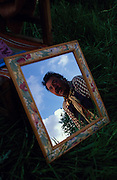 Leslie reflected in picture frame. Romany gypsies, Leslie and Edna traveling with a traditional bowtop wagon in the English countryside...English Romany Gypsies traditionally traveled the country roads camping nearby towns and villages, choosing the grassy roadside banks, where they tethered their horses, or in farmer's fields, when they were allowed. Travelling in bowtop wagons drawn by horses, and before that with tents, sometimes with horse drawn carts or just by foot. Often they worked as casual agricultural labourers, doing the seasons work. They also could earn their living in different ways, sometimes selling their wares, brass, tin, wood and cloth, such as embroidered cloths or lace, telling fortunes, music and dancing, and through crafts skills in basket making, plaiting chair bases, sharpening knives,  They would make fires from old wood, cleaning up after them when they moved on. There were several horse fairs, notably Appleby in Cumbria and Stow-on-Wold in the Cotswolds where they trade and sell horses, some traditions which keep to this day.